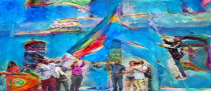 A festive, colorful image capturing a lot of movement shows a group of people of many races and genders in front of a blue building with heads raised looking up as a multi colored rainbow LGBTQ flag is hoisted up by a BIPOC man on a ladder. A BIPOC woman and man stand near a podium addressing the crowd.